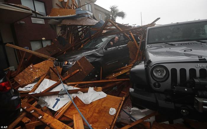 Người đàn ông cùng chiếc xe hơi mắc kẹt giữa đống đổ nát khi một khách sạn tạiPanama City Beach bị hư hại nặng nề do gió bão. Ảnh: AP