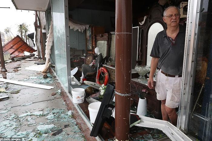 Ông Mike Lindsey đứng trong cửa hàng đồ cổ của mình ở thành phố Panama City khi bão mạnh làm vỡ những tấm kính. Ảnh: Getty