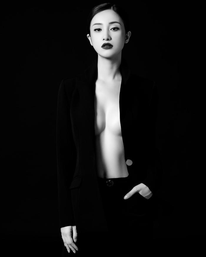Cô nàng chụp cùng suit với gam đen trắng nhưng lại cực quyến rũ khi bung hết tất cả cúc áo khoe vòng 1 đẫy đà và vòng 2 săn chắc.
