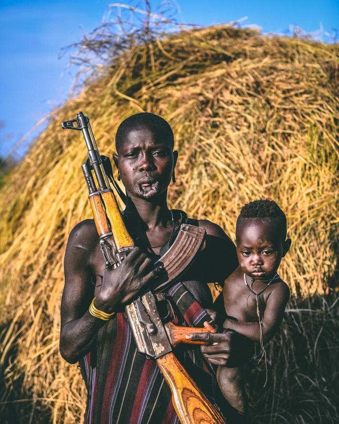 Người phụ nữ bộ lạc Mursi một tay cầm khẩu súng AK-47 và một tay bế con.Súng thường được sử dụng như một vật dụng truyền thống để họ có thể tự bảo vệ mình trước những xung đột bộ tộc.