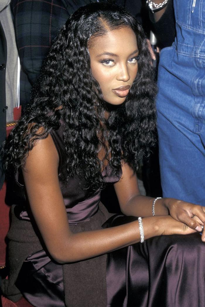 Siêu mẩu Naomi xuất hiện đằng sau cánh gà năm 1997 với tóc xoăn dài, môi tô son bóng và lông mi dày.
