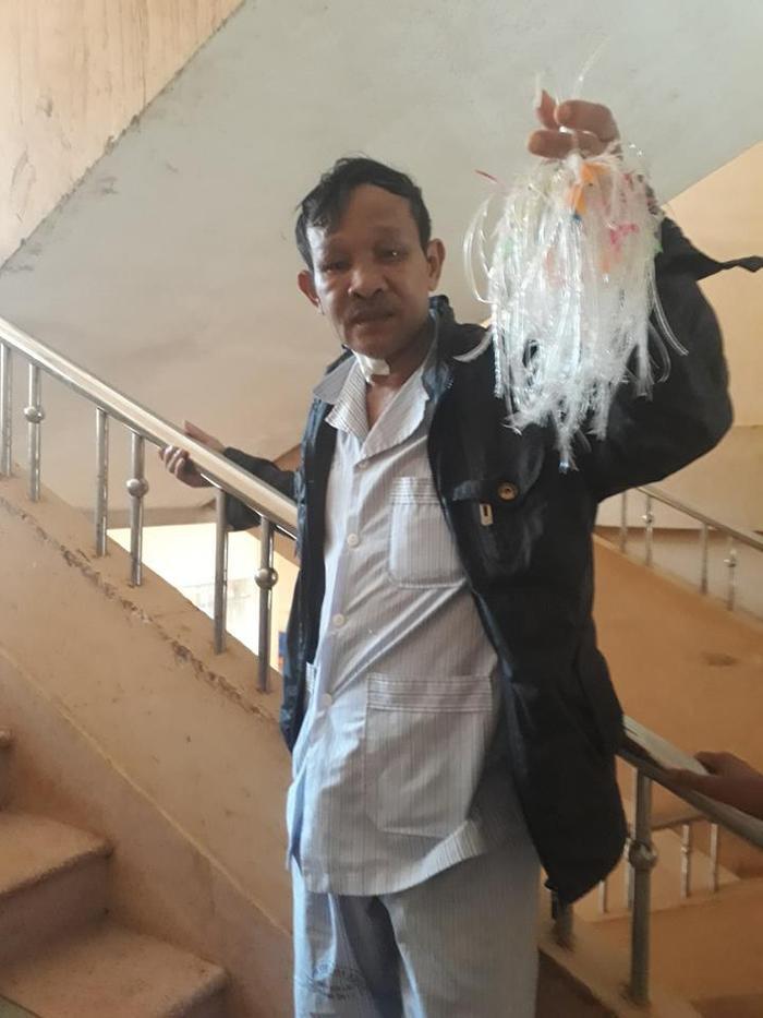 Trong những ngày nằm viện, người đàn ông vẫn gắng gượng thắt từng con cá nhựa để bán kiếm tiền – (Ảnh: Hoa Cói).