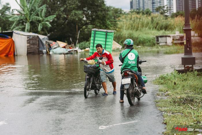 Người dân vất vả để duy chuyển qua đoạn đường ngập nước.