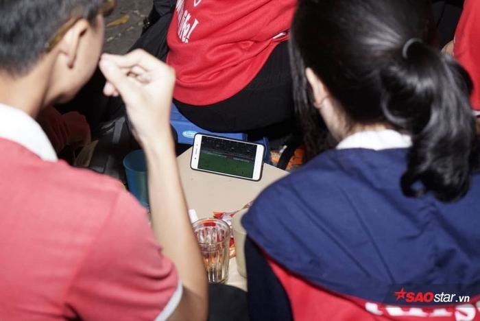 Các bạn sinh viên chăm chú theo dõi trận đấu qua màn hình điện thoại