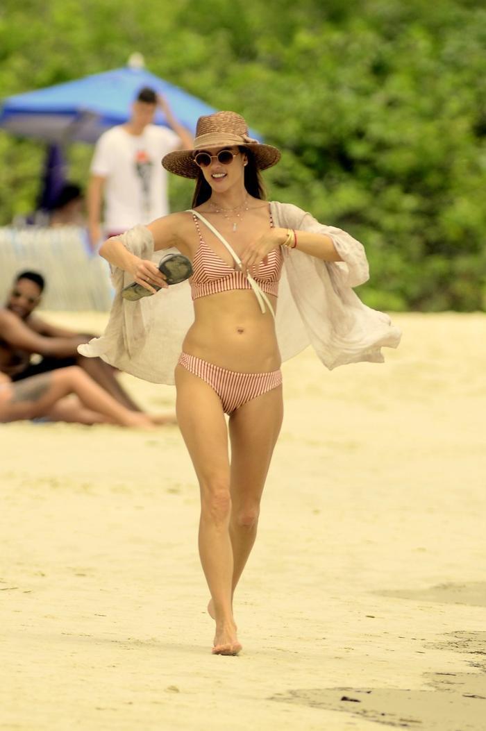 Cựu thiên thần Victoria' Secret thả dáng trong bộ bikini 2 mảnh, kết hợp cùng áo choàng, mũ rộng vành và kính râm.