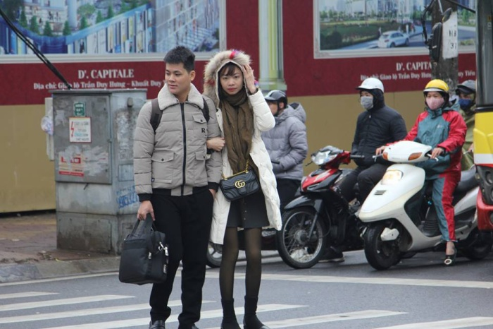 Cặp đôi vội vã bước trên đường phố trong giá lạnh.