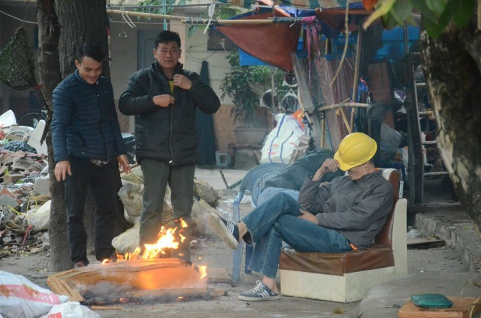 Nhóm công nhân đốt lửa sưởi ấm vào ban ngày ở khu vực chợ Ngã Tư Sở.