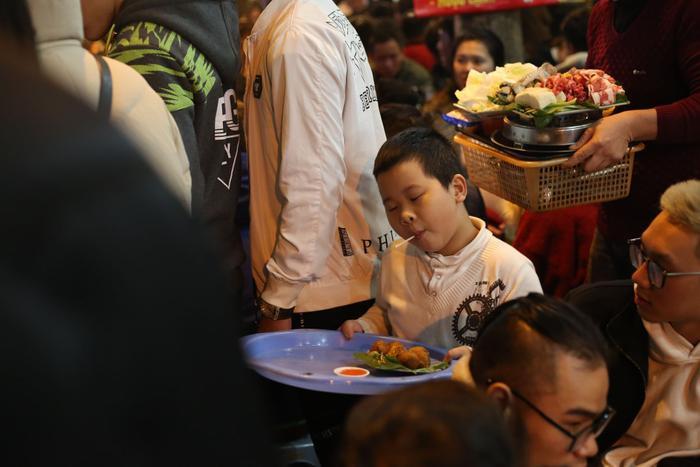 Khách đông, cậu bé ra phụ bố bưng đồ cho khách