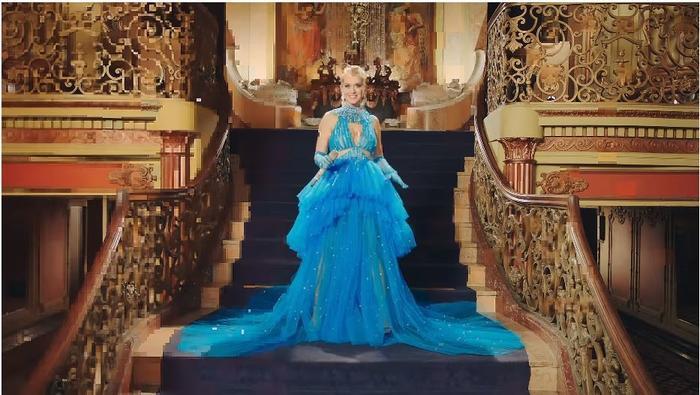 """Thiết kế đầm xanh được thực hiện bởi Công Trí chính là trang phục chủ đạo của Katy Perry trong MV mới """"Final Fantasy"""". Đường khoét lưng sâu, xẻ ngực và cắt bên hông tinh tế giúp Katy Perry vừa phô diễn tấm lưng trần quyến rũ lại tôn được các """"điểm vàng"""" cơ thể với sắc xanh bắt mắt còn khiến giới mộ điệu liên tưởng tới chiếc đầm xanh kinh điển của nàng Lọ Lem trong 'Cinderella"""""""