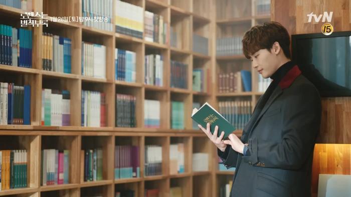 Ở đoạn giới thiệu thứ hai, Lee Jong Suk đứng dựa vào tường và chăm chắn đọc một quyển sách.