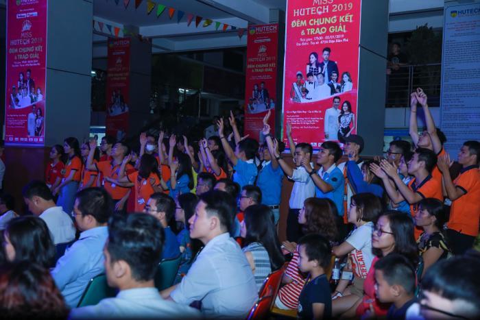 Các cổ động viên giơ cao cánh tay theo điệu nhạc trên sân khấu.
