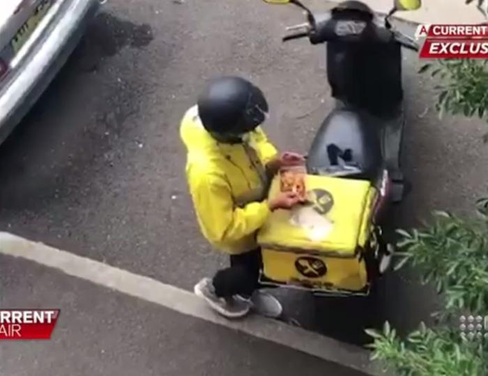Nhân viên giao hàng lén ăn đồ ăn của khách.
