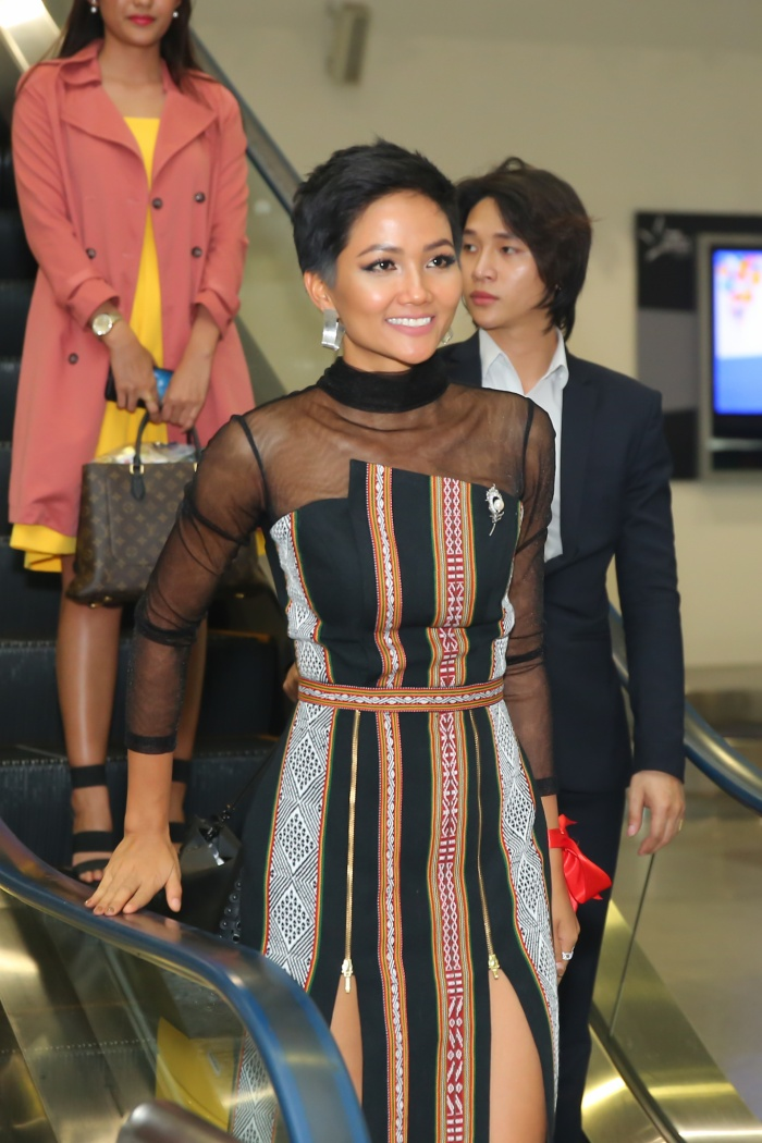 """Sau nửa tháng tranh tài ở xứ sở chùa vàng, ngay khi vừa đặt chân xuống sân bay Tân Sơn Nhất, top 5 Miss Universe đã """"mở hàng"""" bằng một thiết kế cũ. Bộ cánh lấy cảm hứng từ trang phục dân tộc Ê Đê được đã được cô diện trên đất Thái Lan."""