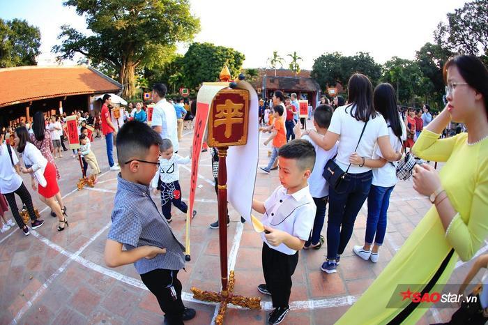 Trẻ em theo chân cha mẹ đến Văn miếu.