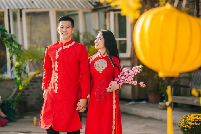"""Không thua kém gì bạn gái, """"Vua dội bom"""" Tiến Linh cũng diện một chiếc áo dài màu đỏ giống người yêu. Đôi """"trai tài gái sắc"""" này không ngại nắm tay và dành cho nhau những cử chỉ ngọt ngào trên đường phố."""