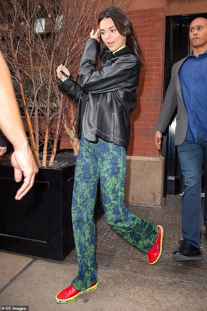 Kendall Jenner chọn lối makeup nhẹ nhàng, mặc áo khoác da phối cùng quần ôm màu ombre họa tiết giản dị mix thêm cùng giày đỏ thể thao.