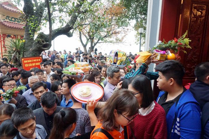 Nhiều dân công sở chuẩn bị tiền vàng, lễ cúng. Do quá đông và chen chúc, nhiều người phải đội lễ lên đầu để tìm cách len lỏi giữa dòng người.