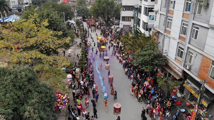 Người dân trải đứng xếp hàng dài dọc 2 bên đường xem màn rước kiệu.