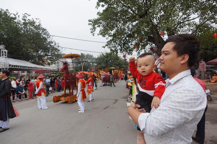 Một em nhỏ được bố đưa đi xem lễ hội.