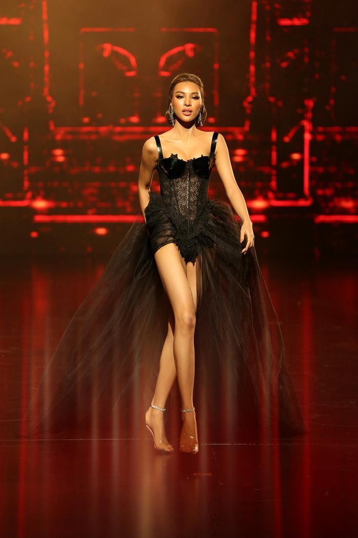 Giữa sân khấu được nhuộm đỏ bởi ánh đèn, Khả Trang sải từng bước kiêu kỳ, cuốn hút. Cô được NTK chọn thể hiện bộ cánh theo dáng corset ôm sát cùng tông đen quyền lực. Thiết kế cắt may vừa vặn giúp tôn lên hình thể quyến rũ, đặc biệt là đôi chân dài miên man.