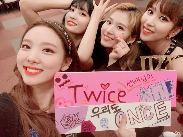 Một số thành viên Twice chụp ảnh cùng banner ITZY tặng.
