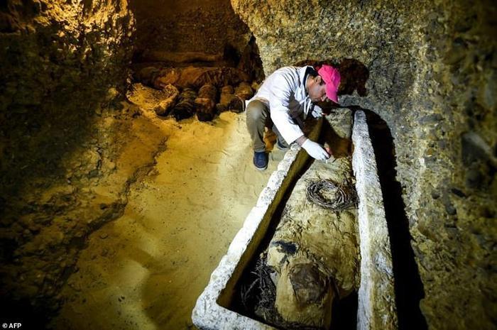 Một nhà khảo cổ đang kiểm tra một quan tài trong lăng mộ mới được phát hiện.