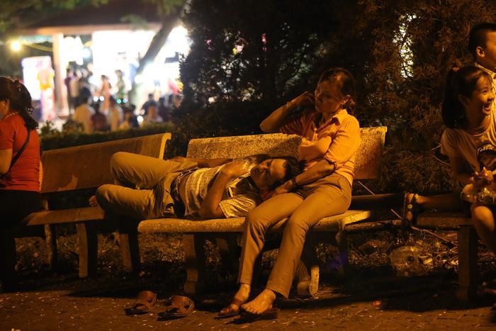 Nhiều người mệt mỏi nằm nghỉ ở ghế đá ven đường