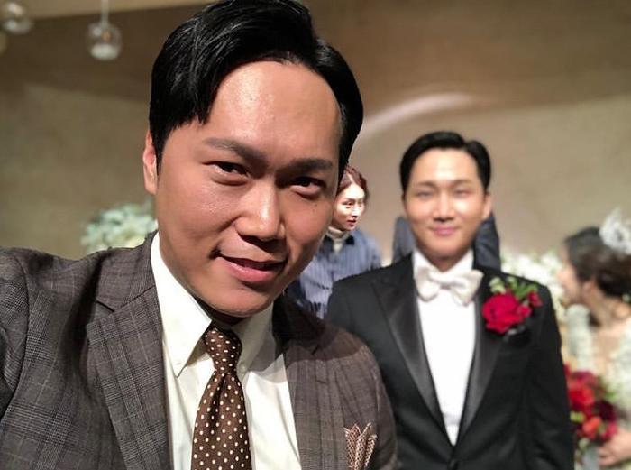 Chú rể bị làm mờ, lấy nét rõ mặt Kim Hee Chul. Anh đang trò chuyện với cô dâu.