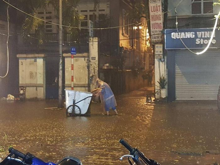 Người lao động vất vả mưu sinh dưới cơn mưa lớn lúc nửa đêm này.