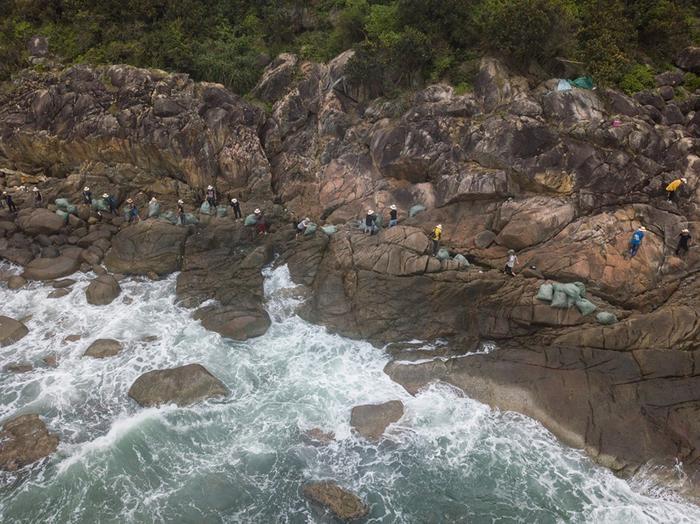 Những túi rác được chuyển bằng tay dọc sườn núi đá