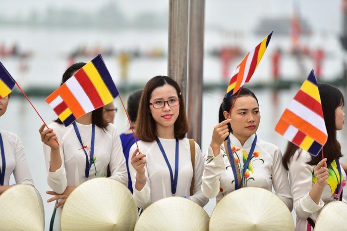 Nhiều người cầm cờ chào đón đại biểu.