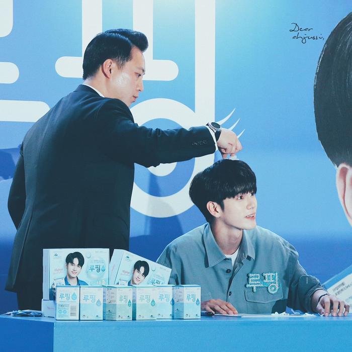 Ahjussi giúp Ong Seongwoo gỡ hoa giấy trên đầu.