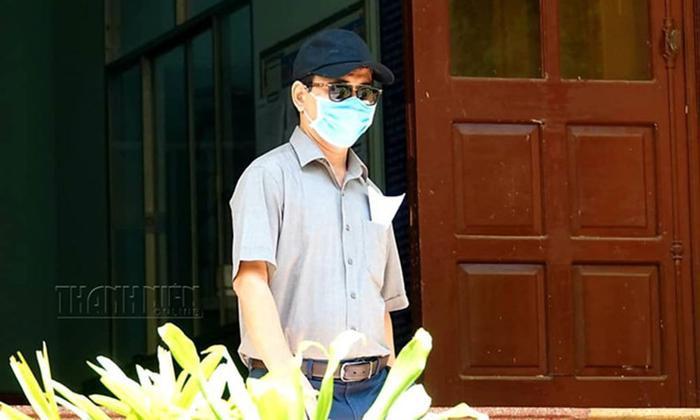 Nguyễn Hữu Linh bịt kín mặt để tới tòa nhận quyết định triệu tập. Ảnh: Theo Thanh Niên