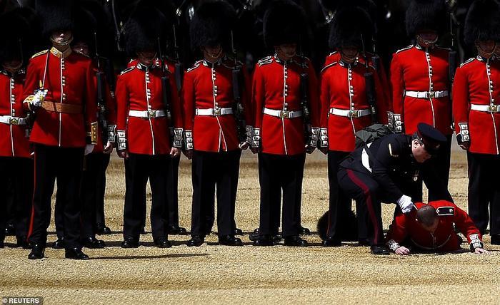 Một lính gác ngã gục giữa trời nóng khi đang tham gia vòng diễn tập thứ hai trước ngày sinh nhật chính thức của Nữ hoàng. Nữ hoàngElizabeth II là người trị vì tại vị lâu nhất trong lịch sử nước Anh.Nữ hoàng luôn được tổ chức hai ngày sinh nhật trong năm, một ngày với người thân và một ngày trên toàn vương quốc. Ảnh: Reuters