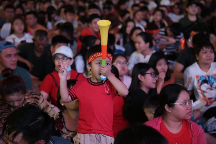 Một bé trai đang thổi còi để khuấy động không khí trận đấu.