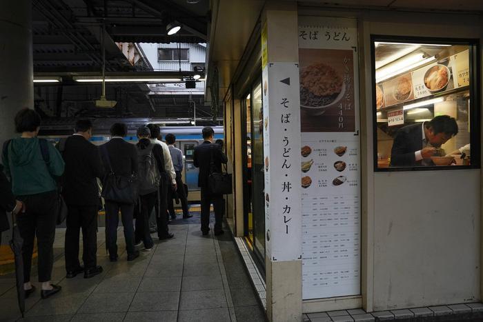 Một quán mì nhỏ đặt tại nhà ga bên cạnh dòng người đang xếp hàng chờ lên tàu.