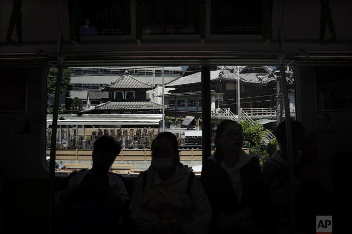 Một nhóm các du khách nước ngoài đang ngồi trên tàu trong khi con tàu đi ngang qua ngôi chùa Phật giáo ở Hamamatsucho.