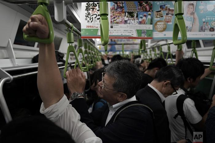 Một người đàn ông tỏ ra khó chịu trong chuyến tàu chật cứng người vào buổi sáng trước khi bắt đầu ngày làm việc mới.