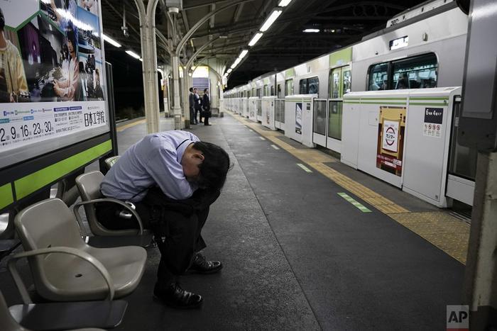 Nhân viên công sở ngồi gục xuống đùi để chợp mắt nghỉ ngơi trong khi đợi chuyến tàu đưa anh đến công ty.