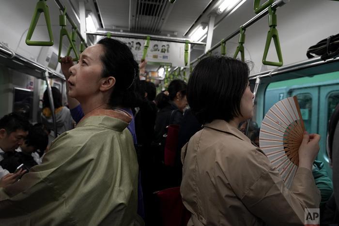 Một người phụ nữ mặc kimono đứng cạnh những người mặc trang phục hiện đại.