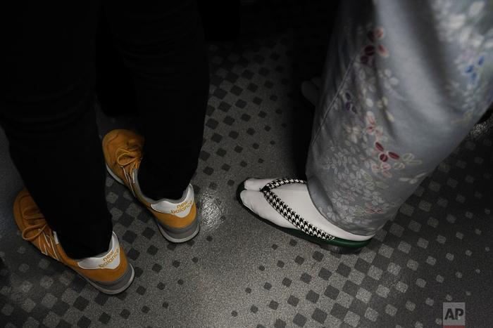 Đôi guốc truyền thống mặc cùng với kimono của người phụ nữ bên cạnh đôi giày thời trang của một người trẻ.
