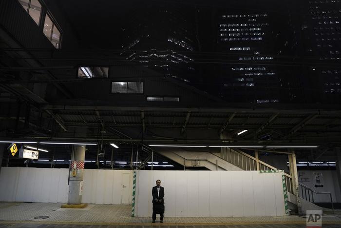 Người đàn ông đứng một mình giữa không gian rộng, vắng vẻ và yên tĩnh để chờ chuyến tàu tiếp theo.