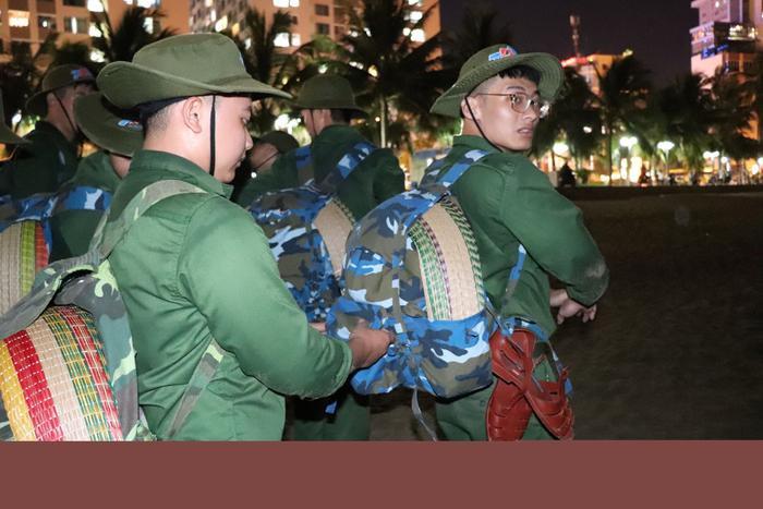 Hình ảnh đồng đội chỉnh trang lại balo cho nhau trước khi lên đường hành quân.