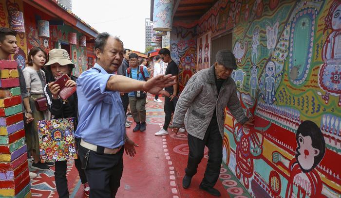Nhân viên an ninh đang hộ tống ông Hoàng trở về nhà sau một buổi giao lưu với khách du lịch. Ảnh: Rachel Chung/SCMP.
