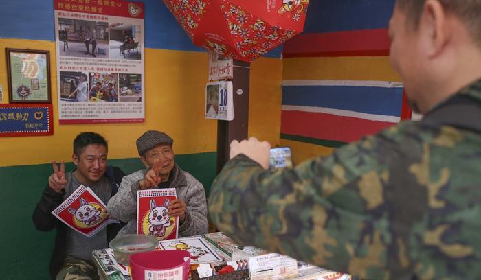 Ông Hoàng đang tạo dáng cùng với du khách bên cạnh những tác phẩm nghệ thuật của mình. Ảnh: Rachel Chung/SCMP.