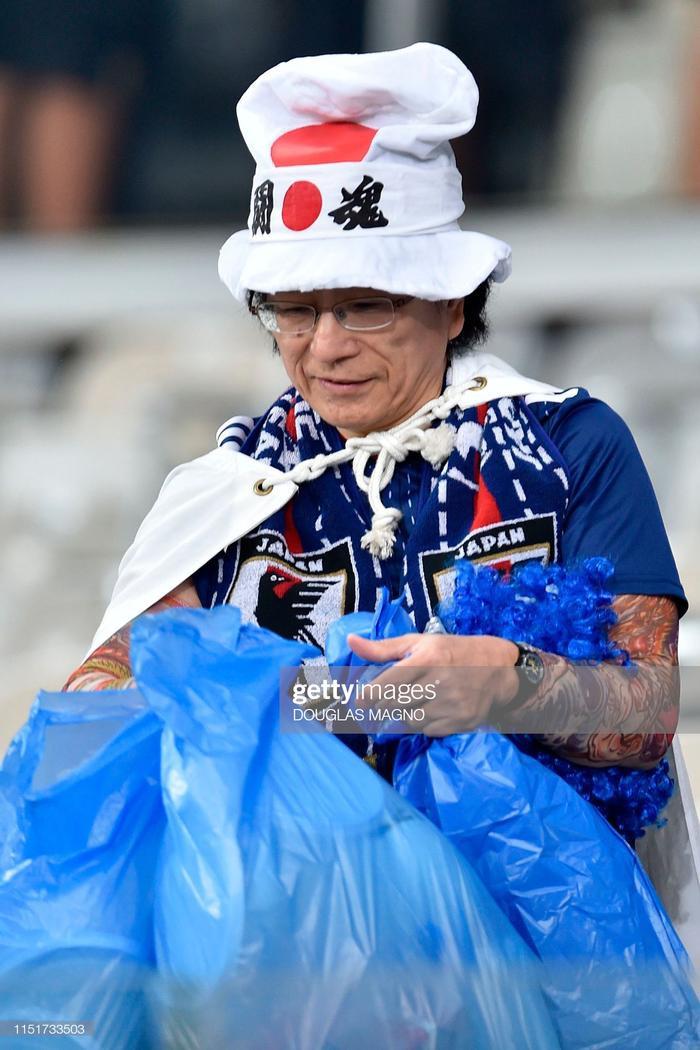 Một CĐV Nhật Bản đi thu gom rác thải do người hâm mộ để lại trên khán đài sân Estadio Pinto.