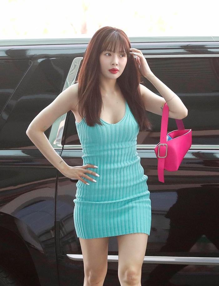 HyunA xuất hiện tại sân bay trong chiếc váy bó sát màu xanh cùng với chiếc túi hồng vô cùng nổi bật