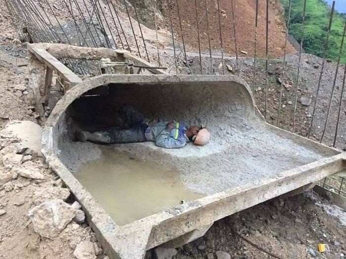 Người công nhân tranh thủ nghỉ trưa khi vẫn còn vận nguyên bộ quần áo lấm lem dính đầy xi măng, đất bẩn.