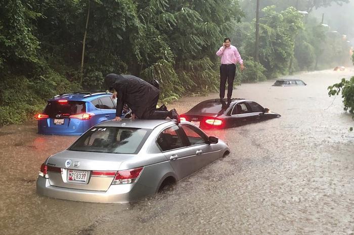 Nhiều xe ô tô bị chết máy trên đường, các tài xế phải trèo lên nóc xe để gọi cứu hộ.