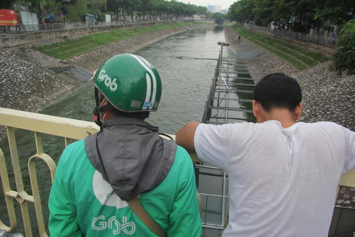 Nhiều người Hà Nội thích thú nhìn ngắm dòng sông Tô Lịch chuyển màu xanh lạ kỳ.